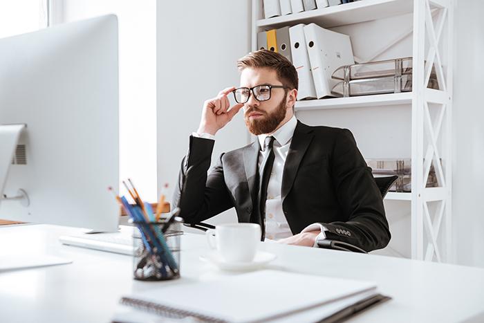 Muškarac koji nosi progresivne naočare dok radi za računarom